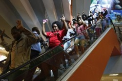 k53-Shoppers-hurry-down-an-escalator-with-their-hands-in-the-air-as-they-make-their-way-out-of-the-shopping-centre-to-safety-452x300